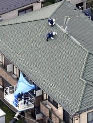女性が刺殺されたアパートの屋根などを調べる捜査員ら(28日午後、東京都杉並区)=共同
