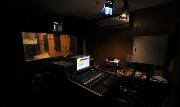 原稿を読む「ナナコ」の画面が薄暗いスタジオに光る