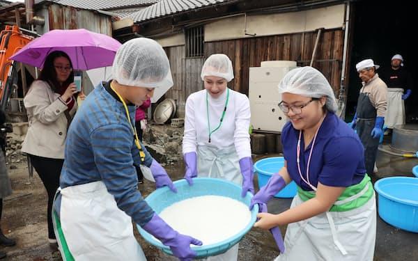 酒蔵で酒造りを体験する(左から)日本人、アメリカ人、フィリピン人の学生(大阪府阪南市)