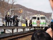 鉄道ファンが見守る中、夕張駅を出発するJR夕張支線の列車(31日、北海道夕張市)