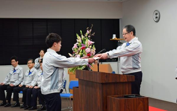 トヨタ自動車東日本の入社式で新入社員へ辞令を手渡す白根社長(1日、宮城県大衡村)