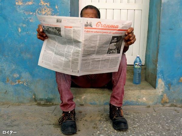 共産党機関紙「グランマ」を読む男性(ハバナ)=ロイター