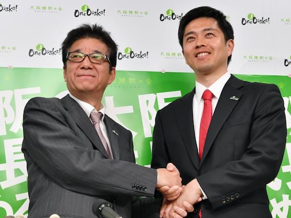 当選を決め、記者会見で握手する松井一郎氏(左)と吉村洋文氏(7日夜、大阪市中央区)