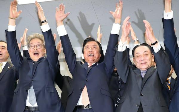 福岡県知事選で当選を決めバンザイする小川氏(中)(7日午後、福岡市博多区)