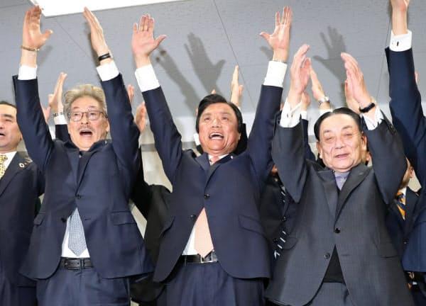 福岡県知事選で当選を決め、万歳する小川洋氏(中)=7日夜、福岡市博多区