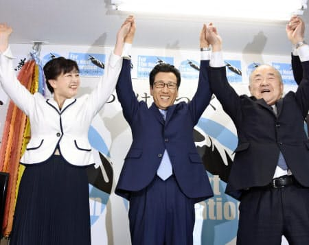 札幌市長選で再選を決め、万歳する秋元克広氏(中央)(7日夜、札幌市中央区)=共同
