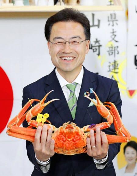 福井県知事選で初当選を決め、越前ガニを手に笑顔を見せる杉本達治氏(7日夜、福井市)=共同