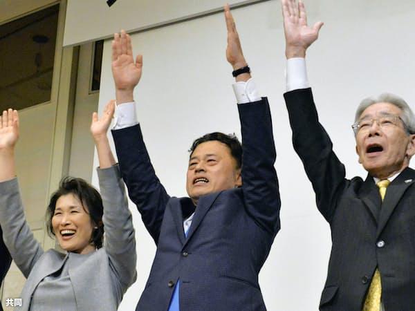 島根県知事選で当選を決め、万歳する丸山達也氏(7日夜、松江市)=共同