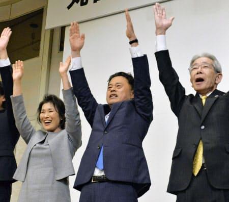 島根県知事選で当選を決め、万歳する丸山達也氏(中央、7日夜 松江市)=共同