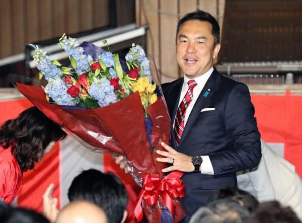 三重県知事選で当選を決め、花束を手にする鈴木英敬氏(7日夜、三重県津市)