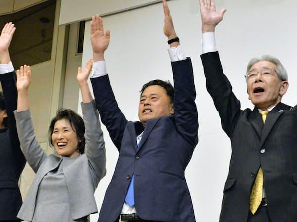 島根県知事選で当選を決め、万歳する丸山達也氏(中央、7日夜、松江市)=共同