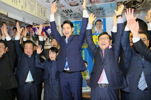 北海道知事選の当確の一報を受け、万歳三唱する鈴木直道氏(中)(7日、札幌市)