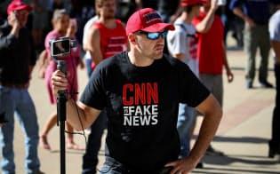 「CNNはフェイクニュースだ」と書かれたTシャツを着るトランプ大統領の支持者=ロイター
