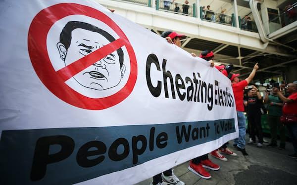 街頭デモで軍政や選管に抗議する横断幕(3月、バンコク)=三村幸作撮影