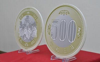 2色を組み合わせた500円硬貨の新デザインも発表された。写真は見本(9日午前、財務省)