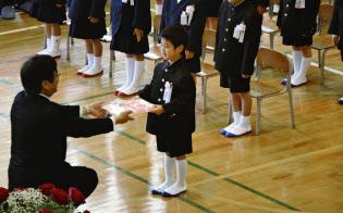 岡山県倉敷市で行われた市立箭田小の入学式で、校長から教科書を受け取る新入生(9日午前)=共同