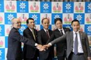 記念撮影に応じる岡山市の大森市長(中央)と中国銀の宮長頭取(左から2番目)ら(9日、岡山市役所)