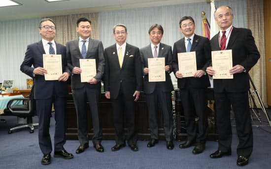 「5G」の割り当て認定書を受け取った携帯各社の社長と石田総務相(左から3人目)=10日午後、総務省