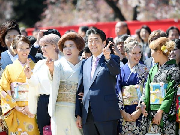「桜を見る会」で参加者とポーズをとり、写真に納まる安倍首相(13日午前、東京・新宿御苑)