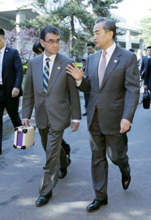 「日中ハイレベル経済対話」の会場に歩いて向かう河野外相(左)と中国の王毅国務委員兼外相(14日、北京)=代表撮影・共同