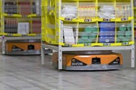 米アマゾンの物流拠点ではロボットがアルゴリズムに基づき何千もの棚を適時、適切な場所に運んだり、並べ替えていく=AP