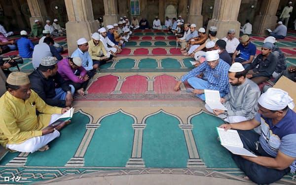 モスクでの礼拝で聖典コーランを読むインドのイスラム教徒(西部アーメダバードで)=ロイター