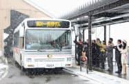 吹雪の中、扇沢駅で行われた電気バスの出発式(長野県大町市)=共同