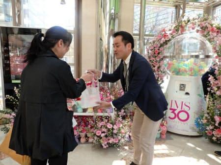 開業30周年の記念品を来館者に手渡しする古場館長(12日、福岡市)