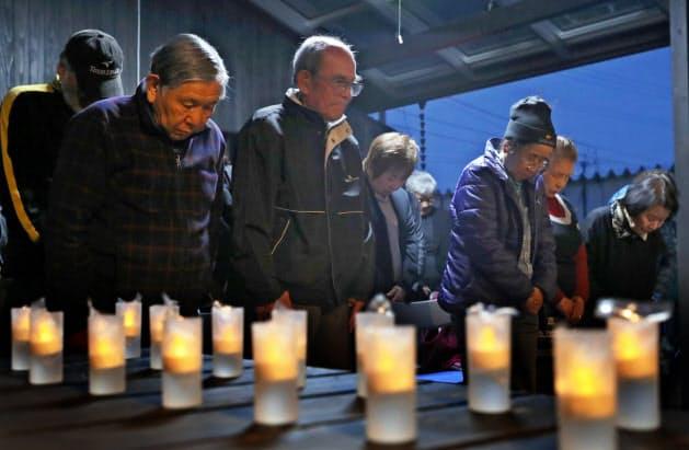 犠牲者の冥福を祈り、黙とうする人たち(14日、熊本県益城町のテクノ仮設団地)