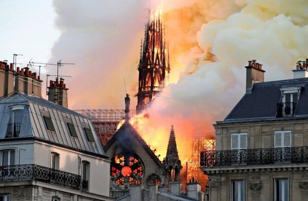 激しく燃えるノートルダム寺院の尖塔。この後崩れ落ちた(15日、パリ)=ロイター