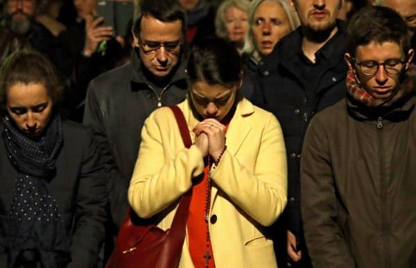 炎上するノートルダム寺院の前で祈る人たち=AP