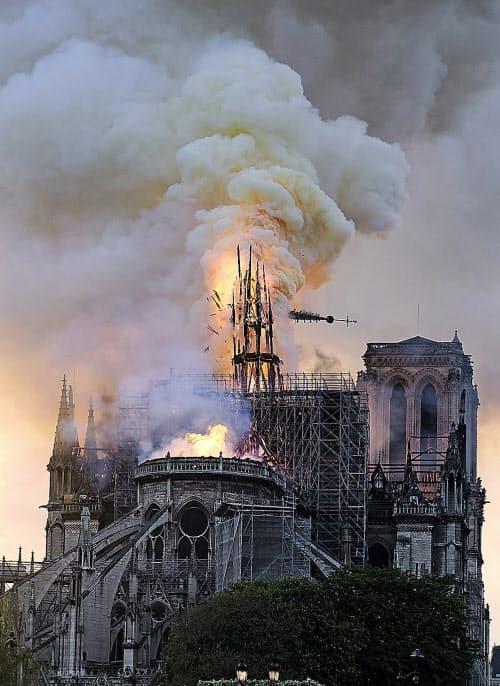 崩れ落ちるノートルダム寺院の尖塔=AP