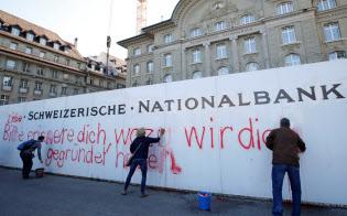 ソブリンマネー構想の是非を問う国民投票で否決後、スイス中銀の前に書かれた推進スローガンを消す人々=ロイター