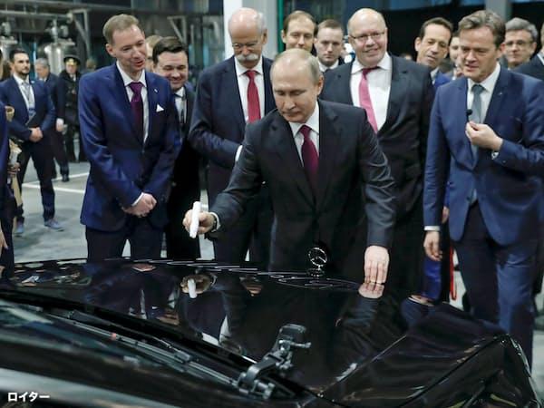 3日、独ダイムラーがモスクワ郊外に建設した新工場の開所式に出席し、車体に記念のサインをするプーチン大統領=ロイター