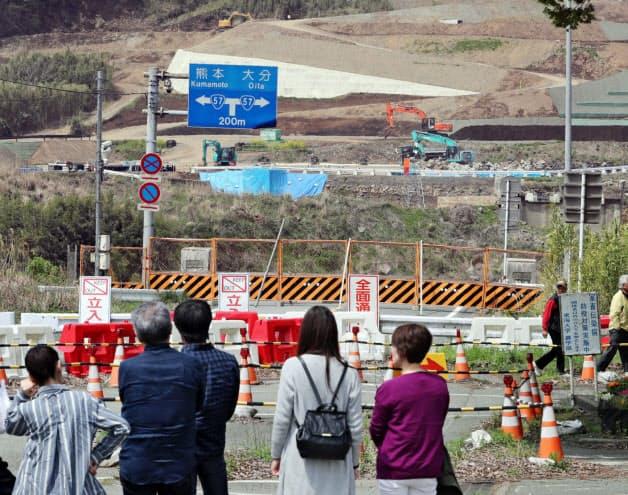 崩落した阿蘇大橋跡で行われる山肌の斜面の復旧工事。約600メートル下流では新しい阿蘇大橋の架け替え工事が進み、2020年度中に完成する予定(16日、熊本県南阿蘇村)