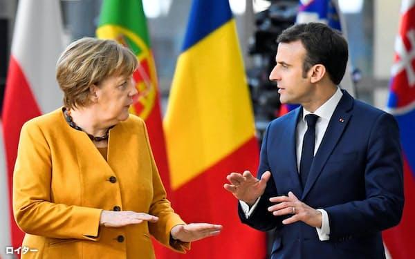 3月22日、ブリュッセルでのEU首脳会議に向かうメルケル独首相(左)とマクロン仏大統領=ロイター