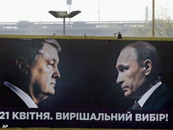 ウクライナ大統領選で劣勢のポロシェンコ現大統領(左)はロシアのプーチン大統領と対峙する看板で支持を訴えた(10日、キエフ)=AP