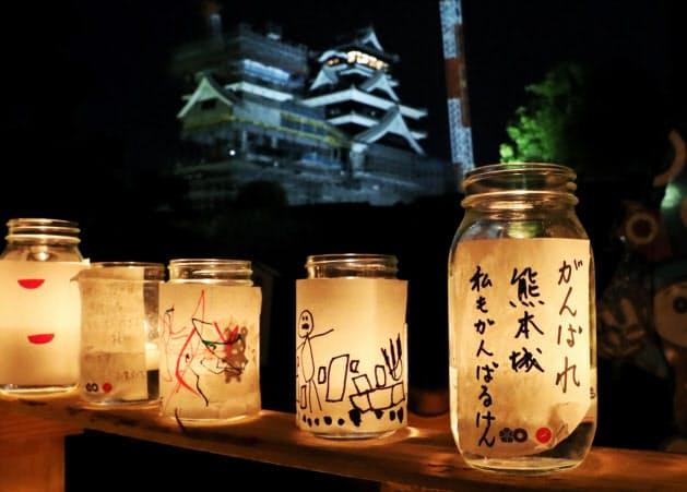 熊本城内の加藤神社に並べられた復興を祈念するキャンドル。奥は復旧工事が進む熊本城(16日夜、熊本市)