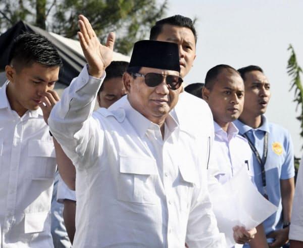 17日、ジャカルタ近郊の投票所に到着し、手を振るプラボウォ氏=共同