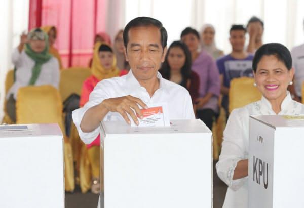 投票するジョコ大統領(左)(17日午前、ジャカルタ)=三村幸作撮影