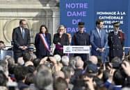 18日、パリで開かれたノートルダム寺院火災の消火活動で活躍した消防隊員らをたたえる式典=ゲッティ共同