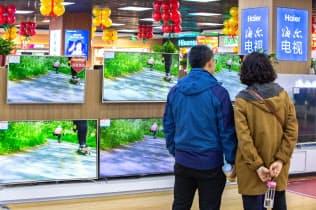 中国の家電販売店でテレビを眺める消費者=AP