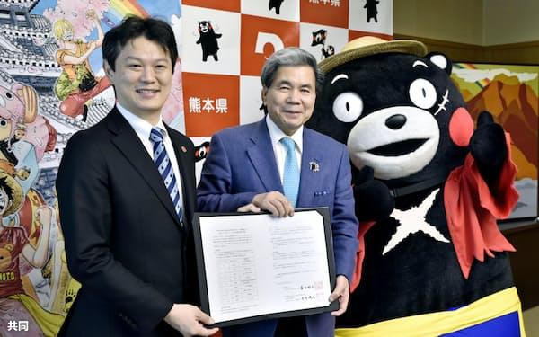 「ONE PIECE」を連載する集英社の中野博之編集長(左)と覚書を交わした熊本県の蒲島郁夫知事(19日午後、熊本県庁)=共同