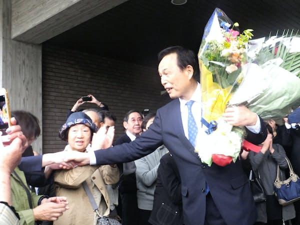 加山氏は花束を手に笑顔で市役所を後にした(19日、相模原市)