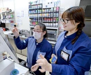 ローソン芝浦八千代橋店でレジ業務を教える中国人の王茜さん(右)(東京都港区)