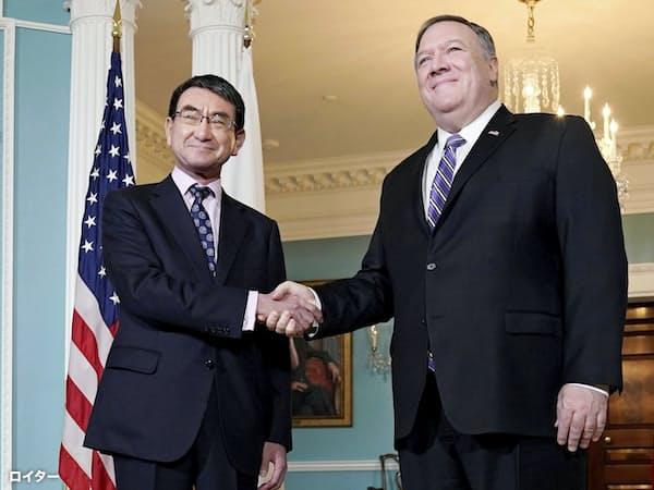 ポンペオ米国務長官(右)と握手する河野外相(19日、ワシントン)=ロイター