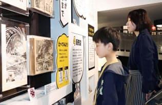 市民向けのプレオープンで展示を見る人たち(20日午後、秋田県の横手市増田まんが美術館)=共同