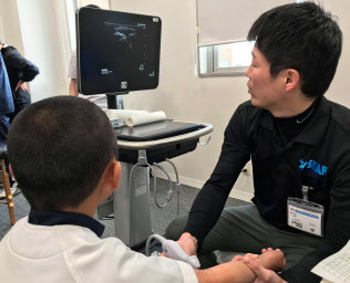 野球少年の肘を超音波検査装置で診る門脇俊医師(島根県出雲市の島根大学病院)