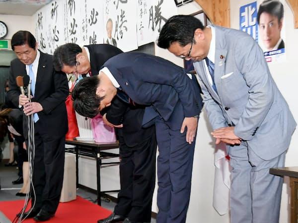 衆院大阪12区補選で落選が決まり、頭を下げる北川晋平氏(右から2人目)=21日、大阪府寝屋川市