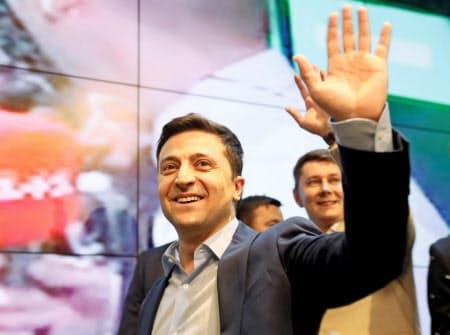 21日、キエフの選対本部で出口調査結果を聞き、勝利を確信して手を振るゼレンスキー氏=ロイター